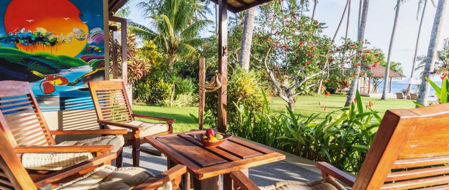 Patio lounge chairs with an ocean view and Balinese art at Villa Joglo at Citakara Sari Estate